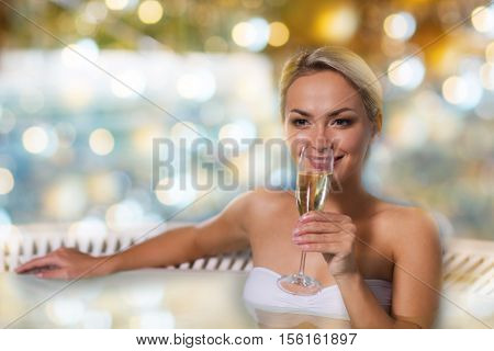 people, beauty, spa and relaxation concept - beautiful young woman wearing bikini swimsuit sitting with glass of champagne in jacuzzi at poolside over holidays lights background
