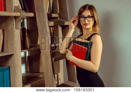young woman librarian in the glasses posing with a book in the library next to the bookshelf and looking at the camera