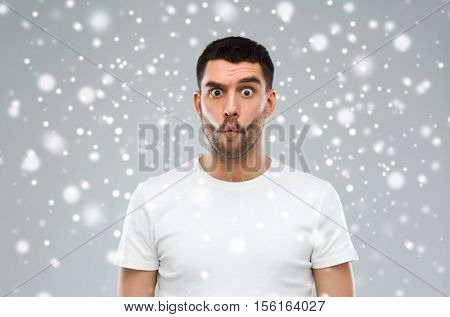 expression, fun, winter, christmas and people concept - man with funny fish-face over snow on gray background