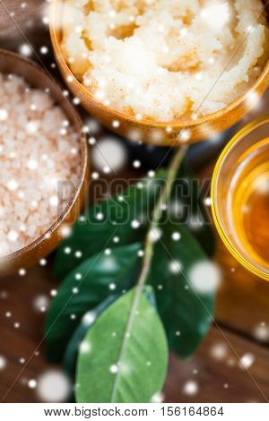 beauty, spa, bodycare, natural cosmetics and wellness concept - close up of body scrub in wooden bowl over snow