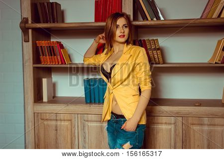 lovely young girl in a yellow jacket unbuttoned posing against the backdrop of a bookcase