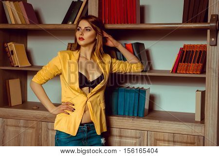 beauty girl in a yellow jacket unbuttoned posing against the backdrop of a bookcase