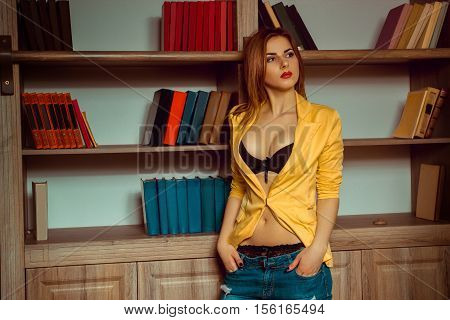 charming girl in a yellow jacket unbuttoned posing against the backdrop of a bookcase