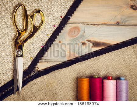 Background with sewing and knitting tools and accesories. Set for needlework placed on flax fabric. Image taken from above, top view. A lot of copyspace.