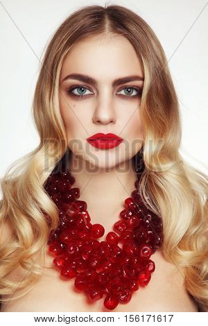 Portrait of young beautiful glamorous woman with blonde curly hair, red lipstick and fancy glass necklace