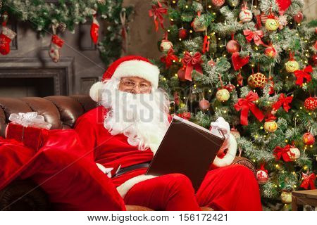 Santa Claus sitting at his home in a comfortable chair and reading a letter. Christmas