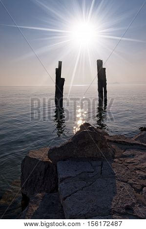 Wharf on the Garda Lake (Lago di Garda - Punta San Vigilio) with sun rays (backlight) and silhouette of wooden bollards. Italy