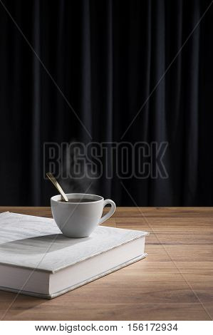 Steaming cup of tea or coffee on white book over wooden table. Dark curtain with copy space in background.