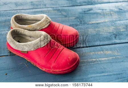 Red rubber galoshes on a blue wooden background
