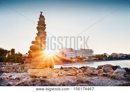 Cairn on seashore shot in front of bright sun