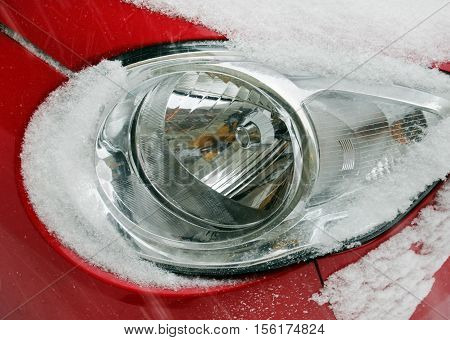 Detail of a red car with round headlights covered with snow during snowstorm