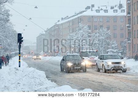 STOCKHOLM SWEDEN - NOV 10 2016: Snow chaos in the traffic in central Stockholm. Cars and people struggeling in the snow. November 10 2016 in Stockholm Sweden