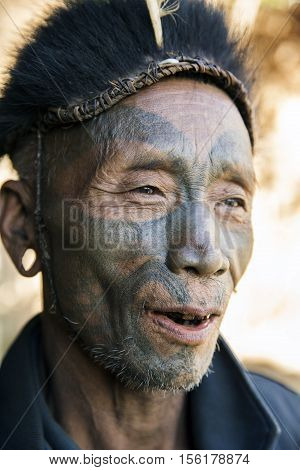 LONGWA, NAGALAND/INDIA - DECEMBER 8, 2013: Tattooed face of elderly former Longwa Village headhunter. Naga tribes practised headhunting & preserved the heads of enemies as trophies.