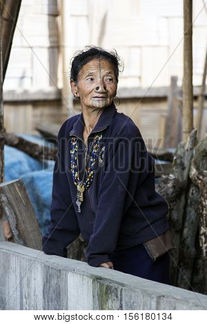 ZIRO, ARUNACHAL PRADESH/INDIA - DECEMBER 14, 2013: Woman of the Apatani tribe, with nose plugs, The Apatani are a tribal group of people living in the Ziro valley in Arunachal Pradesh, India.