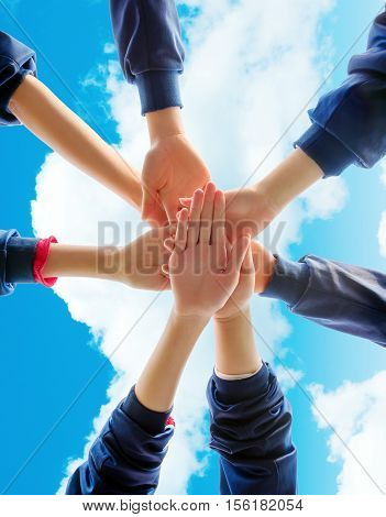Group of young people putting their hands on top of each other. Close up image of young students making a stack of hands.