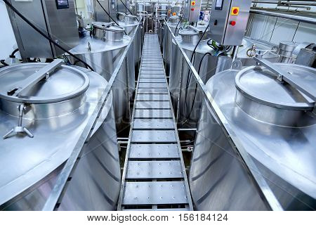 Equipment at modern dairy plant with stainless tanks poster
