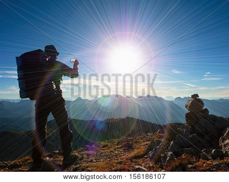 Lens Flare Defect.  Tourist Guide On Alps Peak Takes Photo. Strong Hiker With Big Backpack