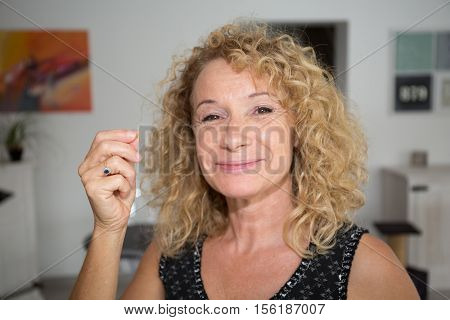 Lovely middle-aged blond woman with a beaming smile sitting on a sofa at home