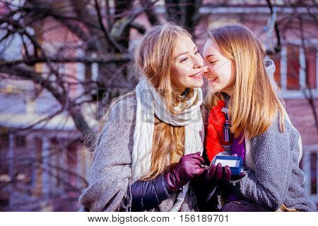 best friends two girls hugging and whispering wearing winter clothes - girl with a gift in hand thanking her friend for a present on winter day- concept of affection and friendship forever