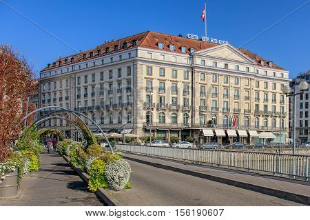 Geneva, Switzerland - 24 September, 2016: view along the Pont des Bergues bridge over the Rhone river, Hotel des Bergues building in the background. The city of Geneva is the capital of the Swiss Canton of Geneva.