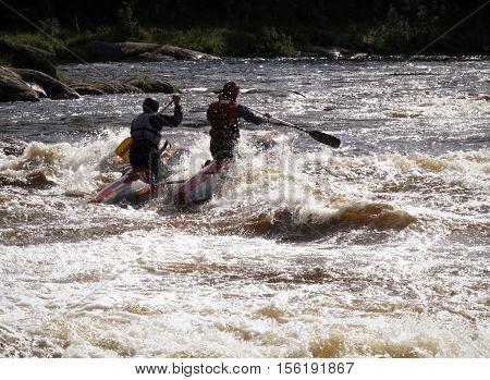 KOLA PENINSULA RUSSIA - 17 AUGUST 2008: Men on an inflatable catamaran overcome the threshold of the turbulent river