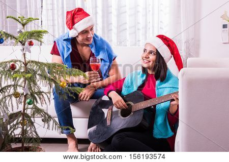 indians celebrating christmas, young indian man sitting on white sofa and girl playing guitar and singing song, merry christmas, christmas celebration and music
