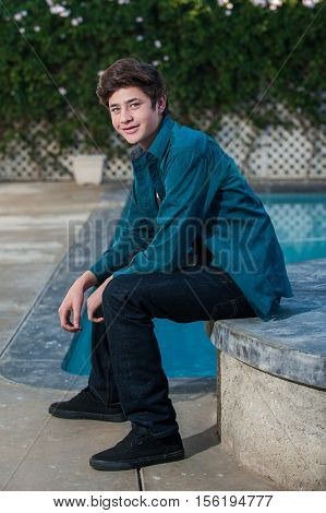 Handsome Latino teen smiling while seated near edge of pool.
