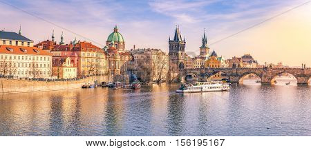 Prague panorama with its river and buildings - Panorama of Prague city the capital of Czech Republic with the Vltava river the Charles Bridge and surrounding buildings on a sunny day of March.
