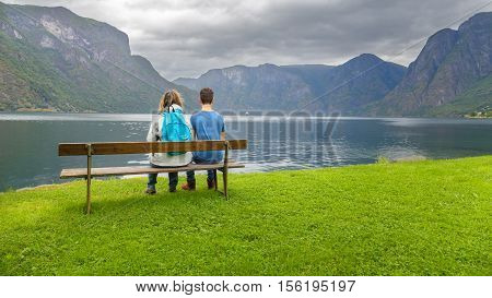 Mother and son sitting on a bench looking at the fjord in Ulvik Norway