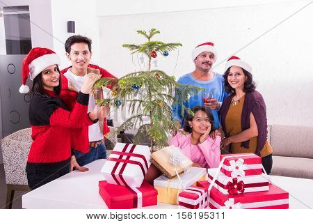 family, christmas, holidays and people concept - happy indian kids decorating christmas tree, while elder brother and sister sitting on white sofa, four indian young siblings celebrating christmas