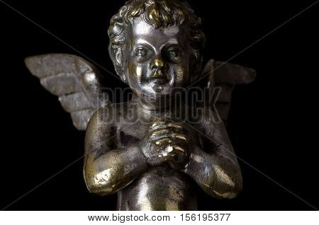 Praying winged putto on black background. Angel made of brass, covered with silver, as part of a candelabra from nineteenth century and symbol for religious passion. Macro object photo front view.