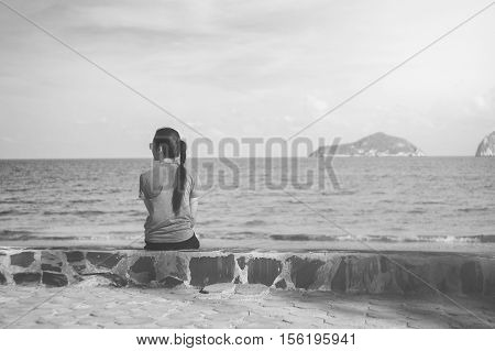 Beautiful Alone Young Asian Woman At Seashore Near The Beach.blurred Sea And Sky In Background.selec