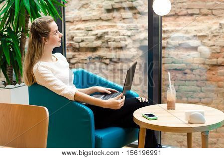 Portrait Of Beautiful Smiling Woman Sitting On A Comfortable Chair In A Cafe With Black Laptop. Pret