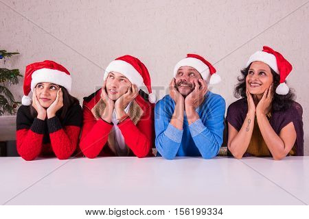 indian goodlooking people  or family celebrating christmas, looking upwards, sitting across white table , hands on chin, red santa hat on heads, presenting / looking at something, christmas in India