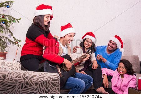 family, christmas , holidays and people concept - happy indian family sitting on sofa and boy playing song on guitar, Indian family celebrating christmas with christmas tree, merry christmas