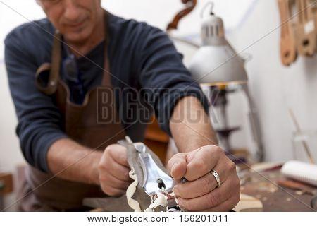 Artisan Lutemaker Working A Violin In His Workshop