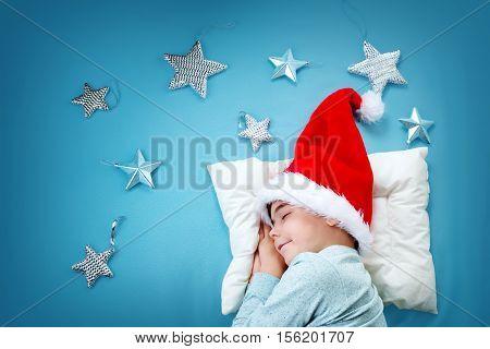 Sleepy child on blue blanket in red hat. Cute boy sleeping in christmas cap