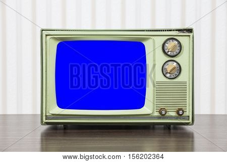 Grungy green vintage television set with chroma key blue screen.