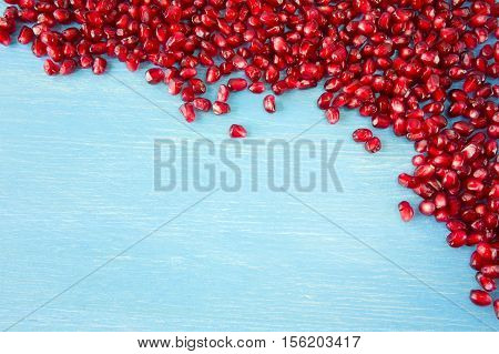 Background made of red pomegranate seeds. The scattered red grains of a pomegranate.