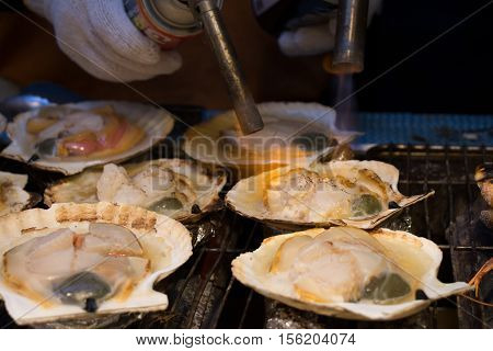 Grilling and burn oysters on flaming fire at Hokkaido morning market. Fresh and Delicious seafood breakfast.