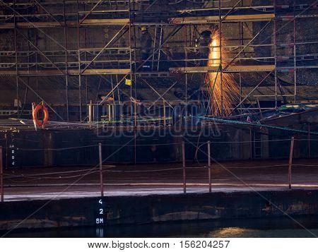 A shipyard steel worker burning steel on scaffolding.