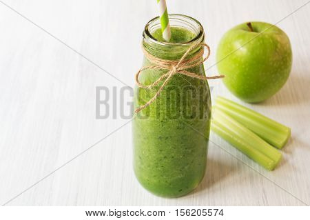 Healthy celery smoothie with green apple in bottle. Green smoothie for weight loss and detox copy space selective focus horizontal