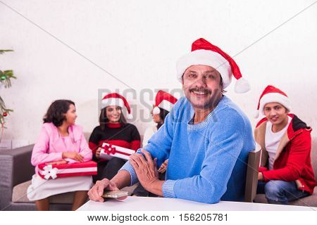 indian man with red santa hat, sitting on table close to camera and family sitting on sofa in the background with christmas tree, Indians celebrating christmas, 25 december, merry christmas