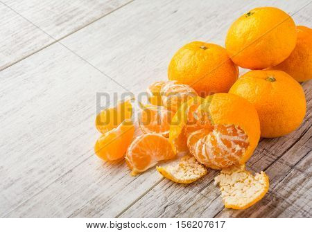 tangerines peeled tangerine and tangerine slices on a white wooden table