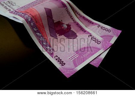 The brand new Indian currency notes of 2000 rupees isolated on black. These have been introduced as part of a drive to curb black money