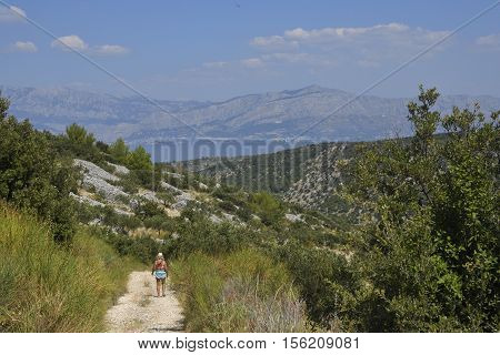 Woman walking on a path in mountain on Brac Island Croatia with mountins and sea and blue sky in background.
