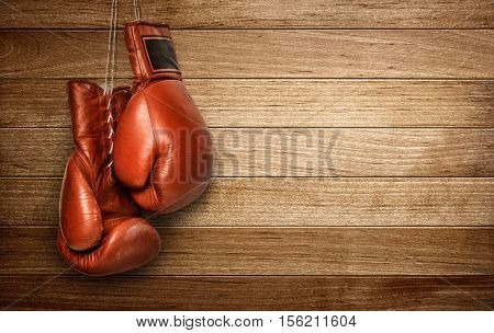 Hang up the gloves, old leather boxing gloves hanged on wooden wall