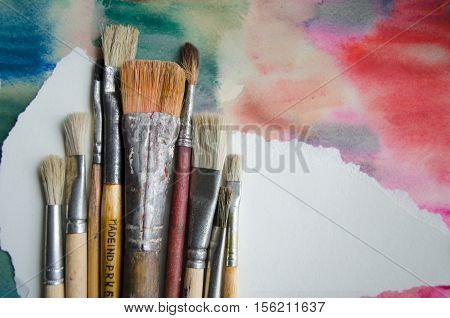 A group of paintbrushes on abstract colorful watercolor background with place for text. Can be used for background banner poster advertising workshops. Blank for motivating quote note message.