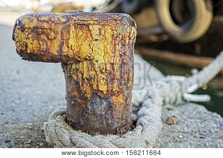 Old Rusty Bollard with Frayed Ship Rope at the Harbor. Nautical Background.
