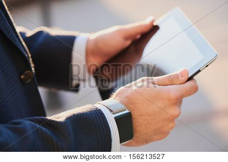 Male hands with smart watch keep tablet